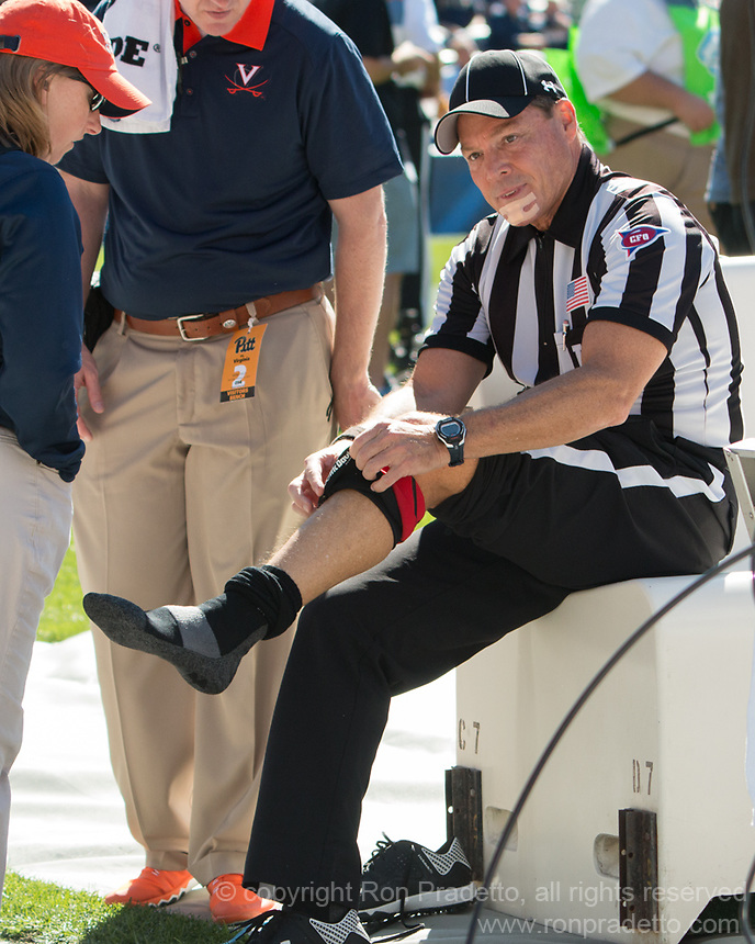 ACC line judge Allen Andrick attends to some of his injuries. The Pitt Panthers football team defeated the Virginia Cavaliers 26-19 on Saturday October 10, 2015 at Heinz Field, Pittsburgh, Pennsylvania.