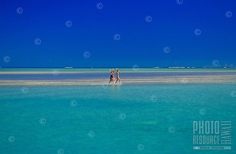 Three woman waving from Ahu o laka  sandbar, on gorgeous Kaneohe Bay, Island of Oahu, Hawaii