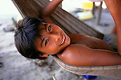 Koatinemo Village, Brazil. Smiling young Assurini Indian boy lying in a hammock.