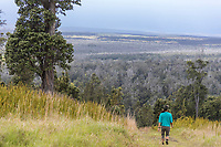A woman walks on a trail at Kahuku Ranch, Hawai'i Volcanoes National Park, Big Island.