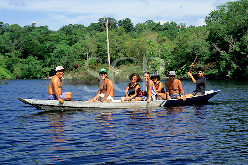 Amazon, Brazil. European tourists in a river boat with local guide visiting a the Eco Park tourist jungle lodge.