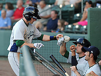 Infielder Zachary Johnson (8) of the Lexington Legends, left, is congratulated in the dugout after scoring a run in a game against the Greenville Drive on May 2, 2012, at Fluor Field at the West End in Greenville, South Carolina. Lexington won, 4-2. (Tom Priddy/Four Seam Images)