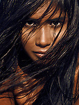Closeup beauty portrait of a young woman face partially covered by long black hair Image © MaximImages, License at https://www.maximimages.com