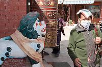 Bodhnath, Nepal.  A Worshipper Wearing a Breathing Mask Circumambulates the Stupa.
