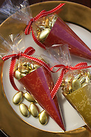 Christmas cones in cellophane and red ribbon are filled with chocolate dragees wrapped in gold foil