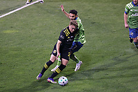 COLUMBUS, OH - DECEMBER 12: Aidan Morris #21 of the Columbus Crew pushes past Cristian Roldan #7 of the Seattle Sounders FC during a game between Seattle Sounders FC and Columbus Crew at MAPFRE Stadium on December 12, 2020 in Columbus, Ohio.