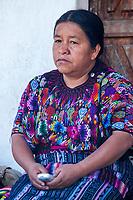 Chichicastenango, Guatemala.  Quiche (Kiche, K'iche') Woman Sitting on Steps of Santo Thomas Church, Holding Cell Phone, Sunday Morning.