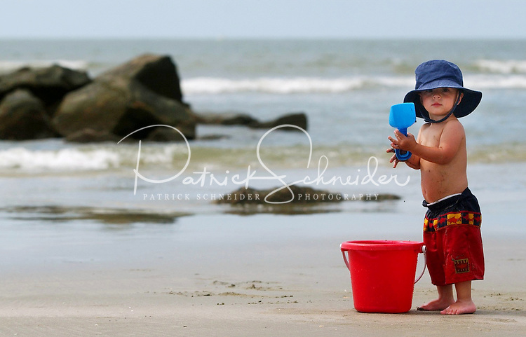 A young boy stands with a bucket and shovel along the beach.