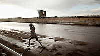 A young girl runs through puddles caused by a heavy rainstorm at a local horse race track in Dodge City, Kansas.