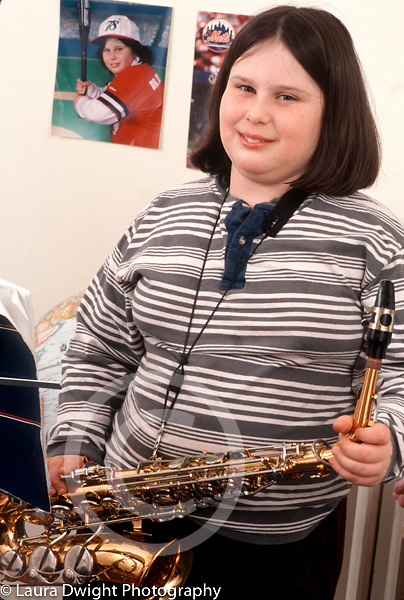 portrait of 10 year old girl holding musical instrument saxophone vertical Caucasian
