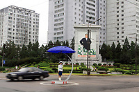 A traffic warden stands n front of a mural of former North Korean leader Kim il-Sung, in downtown Pyongyang.