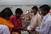 Mourners exchange religious items on the ghats while dead body of their relative burns in the background at the Harishchandra Ghat in the ancient city of Varanasi in Uttar Pradesh, India. Photograph: Sanjit Das/Panos