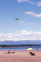"People sunbathing and flying a Kite on the Beach at Qualicum Beach, in the ""Oceanside Region"" of Vancouver Island, British Columbia, Canada"
