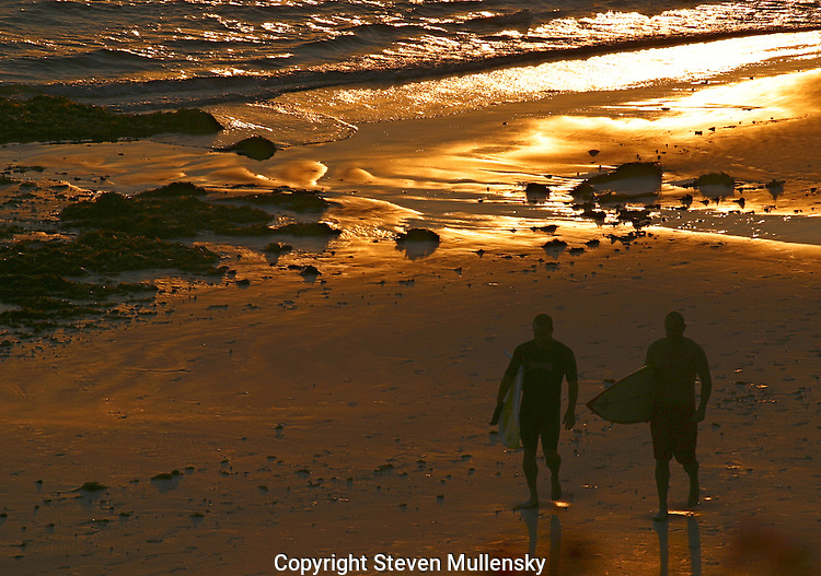 Two surfers head home after time in the water.