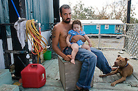 Roy Naquin Jr. holds Jamine Naquin on their porch next to their dog in Pointe Aux Chene, Louisiana. The Naquin family is one of the several families here that identify themselves as Native American. Coastal Louisiana tribes are recognized by the state, but several petitions to be recognized by the federal government have been denied. Many of the families in this region of Louisiana who identify as Native American speak French as a result of their contact with early French settlers, and have lost their native Choctaw language.