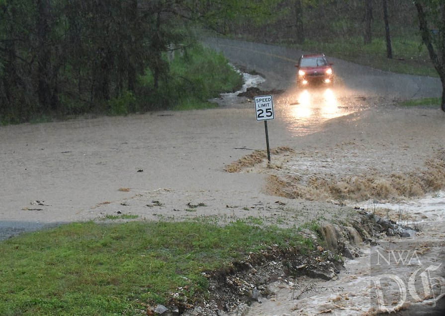 A motorist stops and turns around to avoid a flooded street on Wednesday April 28 2021 in the Prairie Creek community east of Rogers. Go to nwaonline.com/210429Daily/ to see more photos.<br />(NWA Democrat-Gazette/Flip Putthoff)