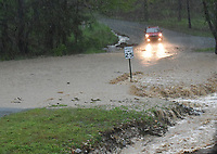 A motorist stops and turns around to avoid a flooded street on Wednesday April 28 2021 in the Prairie Creek community east of Rogers. Go to nwaonline.com/210429Daily/ to see more photos.<br />