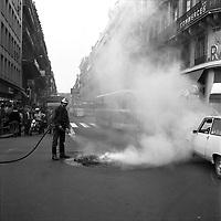 Carrefour de l'avenue d'Alsace-Lorraine et de la rue Lafayette. 5 septembre 1975. Au 1er plan pompier éteignant un feu (pneus) au milieu de la route, fumée ; au 2nd plan deux policiers à moto bloquent la circulation, foule sur le trottoir à l'angle de la rue regarde la scène ; en arrière-plan vue perspective de l'avenue d'Alsace-Lorraine en direction des boulevards, plan d'ensemble des façades, bus. Cliché pris lors d'une manifestation contre le Général Franco.