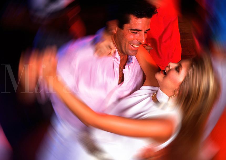 Attractive couple dancing at nightclub.