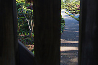 The pathway into the Japanese Gardens, lined with manicured trees and shrubs, is framed by the slates of the closed entry gate.