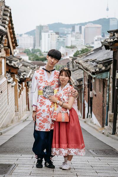 A couple in Hanbok, traditional Korean dress, at Bukchon Hanok Village, Seoul, South Korea. 09.07.16.