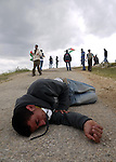 A Palestinian protester collapses from tear gas canisters fired by Israeli soldiers during the weekly demonstration against Israel's controversial separation barrier in the village of Bilin, near the West Bank city of Ramallah on April 22, 2011. Some 250 left-wing Israeli and foreign activists protested in the West Bank village of Bilin against the separation fence being built in the area. Some of the protestors hurled stones at the security forces, who used crowd dispersal means in response. Photo by Issam Rimawi