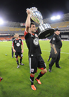 Chris Pontius (13) of D.C. United presenting the U.S. Open Cup Trophy to the fans at  the end of the game.  The Chicago Fire defeated D.C. Untied 3-0, at RFK Stadium, Friday October 4 , 2013.