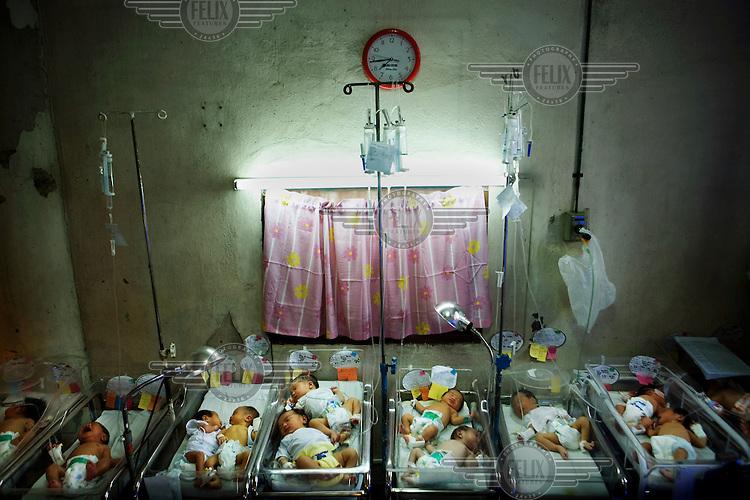 Multiple babies in single incubators in the maternity ward at Jose Fabella hospital.