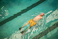 Les Baugh, 59, swims laps in a public pool in Walden, Colorado. While swimming, Les is able to mentally think through commands such as 'extend elbow' or 'rotate wrist'. He will use these when wearing the experimental mind-controlled prosthetic arms which he is testing with John Hopkins Applied Physics Lab. Baugh lost both his arms at the shoulder in a freak electrical accident 40 years ago. Since then, he has managed life mostly without the help of prosthetic arms, which he finds to be more of an uncomfortable nuisance than a help. In 2013, Les underwent a state of the art surgery called Targeted Muscle Reinnervation, where the bundle of nerves at the stump of his shoulders were remapped to his pectoralis muscles. After he recovered from surgery, researchers at Johns Hopkins Applied Physics Lab fitted him with two robotic arms, called the MPL or Modular Prosthetic Limb, and he was able to manipulate objects with his hands, just by thinking about it. The MPL is a state of the art prototype, and not ready for take-home, so Baugh has been practicing mind control at home in rural Walden using a virtual reality game paired with less advanced prosthetic limbs. At a later stage the researchers at Johns Hopkins hope to get Les to try more advanced versions of the MPL  in the hope that his remapped nerves will have grown deeper into his pecs and he'll be able to manipulate the arms more effectively.