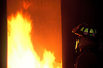 A fire fighter is peering into a room of fire before entering and putting out the fire