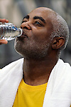 African American man drinking bottled water in gym