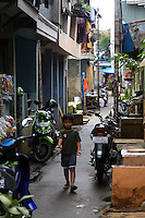 A young boy walks through a small community in central Jakarta.<br />