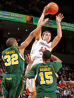 Dec. 20, 2010; Charlottesville, VA, USA; Virginia Cavaliers guard Joe Harris (12) passes the ball over Norfolk State Spartans forward Marcos Tamares (32) and Norfolk State Spartans guard/forward Rodney McCauley (15) during the game at the John Paul Jones Arena. Virginia won 50-49. Mandatory Credit: Andrew Shurtleff