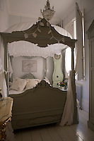 A stylish Swedish four-poster bed dominates the small guest bedroom