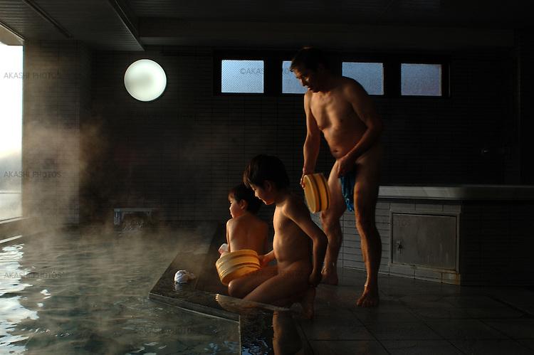 A father and his sons in a Onsen, hot spring bath, in front of Mt. Fuji and Lake Kawaguchi in Yamanashi, Japan.<br /> <br /> Un père et ses fils dans un bain à source chaude Onsen, devant le mont. Fuji et le lac Kawaguchi à Yamanashi, au Japon.