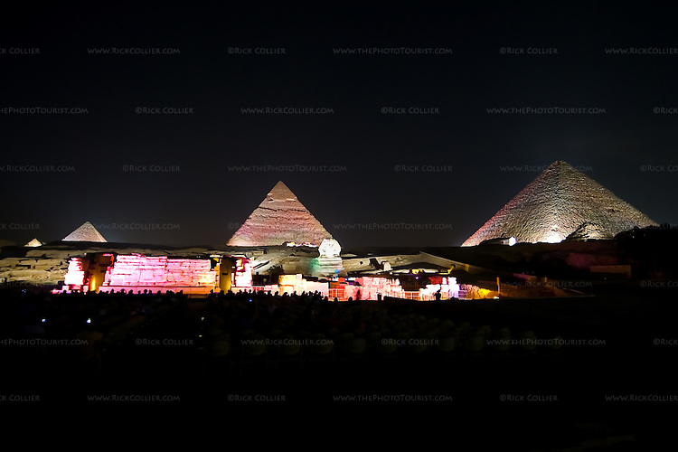 """Giza, Cairo, Egypt -- The three famous pyramids at Giza, surrounded by the """"queen's pyramids"""" and with the remains of the funerary temple of Khafre (Khephren) (featuring the Great Sphinx) are spectacularly illuminated during the famous sound and light show at Giza. © Rick Collier / RickCollier.com"""