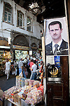 A man works outside his stall selling fruits and nuts beneath  portrait of Syrian President Bashar al-Assad in the Souq Medhat Pasha ,or Straight Street, part of the main shopping bazaar of the Old City.
