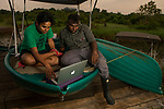 Fishing Cat (Prionailurus viverrinus) biologists, Anya Ratnayaka and Maduranga Ranaweera, reviewing camera trap images in urban wetland, Urban Fishing Cat Project, Diyasaru Park, Colombo, Sri Lanka