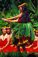 A beautiful female hula dancer from Halau Mohala Ilima performs in a ti leaf skirt with a row of several hula dancers watching.