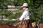 A cowboy riding his horse near an old log cabin