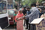 A lady receives her breakfast from one of the members of Kolkata police who are distributing breakfast among the poors of the locality. India is going through a 21 days lockout for Corona virus pandemic. Kolkata, West Bengal, India. Arindam Mukherjee