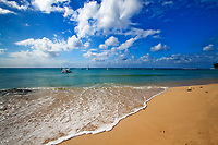 Discovery Bay wave on the golden sand beach, with boats on the turquoise Caribbean Sea, under a blue sky with white clouds, Barbados Island, NA
