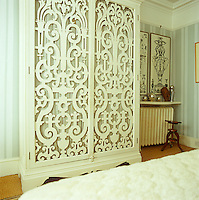 A vast wardrobe in the bedroom is decorated with a pair of carved doors
