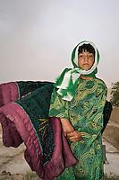 A girl carries mattresses.