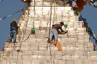 Bodhnath, Nepal.  The All-Seeing Eyes of the Buddha Gaze out from above the Stupa of Bodhnath, a center of Tibetan Buddhism, near Kathmandu.  Workers clean the 13 tapering levels above the dome, representing the 13 stages of perfection leading to nirvana.