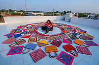 India, Gujarat, Kutch Desert, Bhadroi Village. Pabiben who runs her own textile business, with her bags.