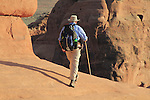 Man hiking at Delicate Arch in Arches National Park, Moab, Utah, USA. .  John offers private photo tours in Arches National Park and throughout Utah and Colorado. Year-round.