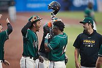 Matthew Fraizer (14) of the Greensboro Grasshoppers is greeted by his teammate after hitting his second home run of the game against the Winston-Salem Dash at First National Bank Field on June 3, 2021 in Greensboro, North Carolina. (Brian Westerholt/Four Seam Images)