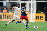 FOXBOROUGH, MA - MAY 22: Andres Reyes #4 of New York Red Bulls pressures Carles Gil #22 of New England Revolution during a game between New York Red Bulls and New England Revolution at Gillette Stadium on May 22, 2021 in Foxborough, Massachusetts.