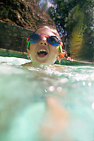 Young boy wearing swimming goggles in a pool, Provence, France.